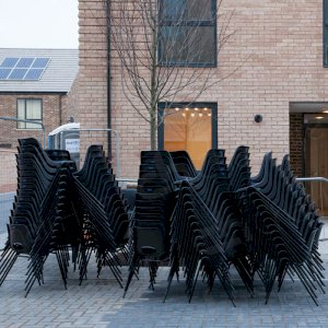 Stacks of black polyprop chairs ready for the evenings event