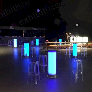Our Illuminated Bar Tables lit up in blue paired with our Charles Ghost High Stools.